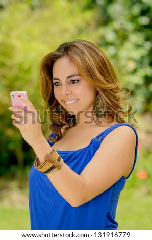 Young beautiful brunette lady touching and browsing her smart phone at the park - stock photo