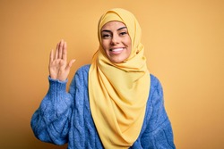 Young beautiful brunette muslim woman wearing arab hijab over isolated yellow background Waiving saying hello happy and smiling, friendly welcome gesture