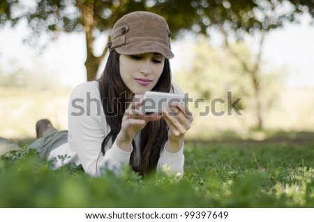 Young beautiful brunette sending a text on her cell phone while resting on hiking trip