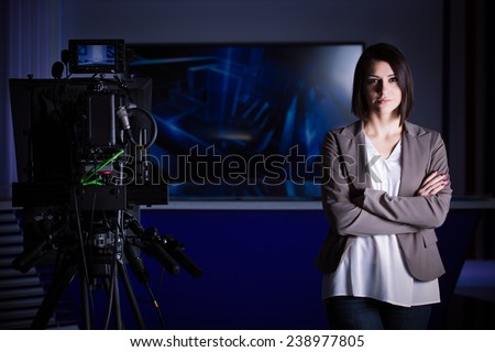 Young beautiful brunette television announcer at studio standing next to the camera.TV director at editor in studio.Recording at TV studio with television anchorwoman. TV NEWS studio with camera.