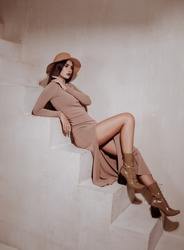 young beautiful brunette wearing tight dress, laquer boots and autumn hat in beige color. fashion model posing on stairs.