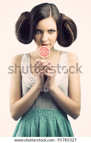 young beautiful brunette with a creative luxury hair style and a colored lollipop. She is in front of the camera, looks in to the lens with an a sly expression and takes the lollipo near the mouth - stock photo