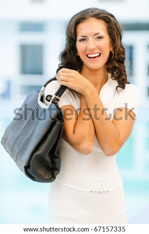 Young beautiful brunette with flowing hair in white clothes has control over ladies' handbag and laughs.