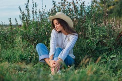 Young beautiful brunette woman dressed in a white sweater, jeans and cowboy straw hat sitting on green grass, smiling and laughing during sunset