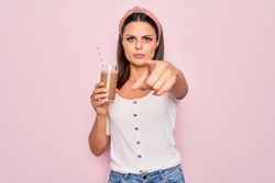 Young beautiful brunette woman drinking glass of chocolate beverage using straw pointing with finger to the camera and to you, confident gesture looking serious
