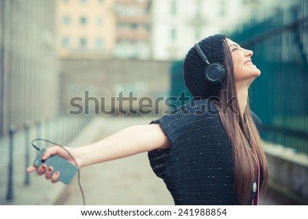young beautiful brunette woman girl listening music headphones outdoor