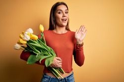 Young beautiful brunette woman holding bouquet of tulips flowers over yellow background Waiving saying hello happy and smiling, friendly welcome gesture