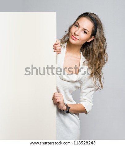 Young beautiful brunette woman holding large empty white billboard.