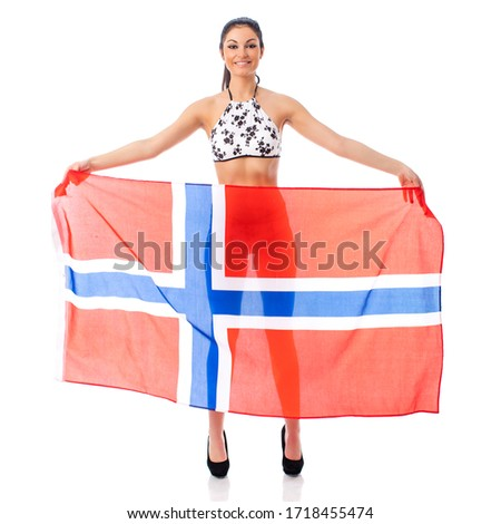 Young beautiful brunette woman in bikini holding a large transparent flag of Norway, isolated on white background