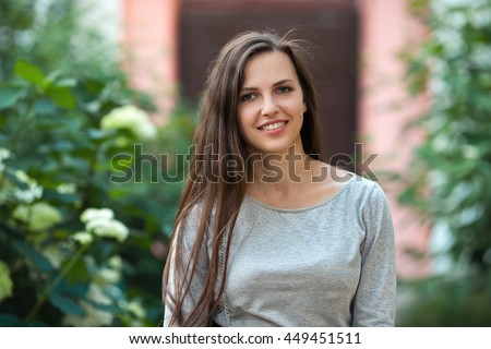 Young beautiful brunette woman in grey blouse standing near hydrangeas outdoors evening