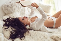 Young beautiful brunette woman in white lingerie reading book in the bed
