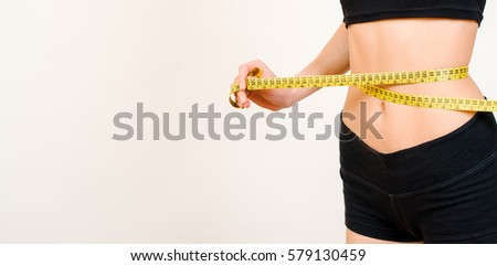 Young beautiful brunette woman measuring her waist with a measure tape isolated on a white background.