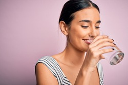 Young beautiful brunette woman smiling happy and confident. Standing with smile on face drinking glass of healthy water to refreshment over isolated pink background