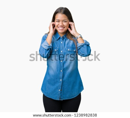 d96591675ca Young beautiful brunette woman wearing blue denim shirt over isolated  background covering ears with fingers with