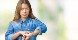 Young beautiful brunette woman wearing blue denim shirt over isolated background In hurry pointing to watch time, impatience, upset and angry for deadline delay