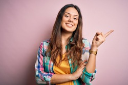 Young beautiful brunette woman wearing casual colorful shirt standing over pink background with a big smile on face, pointing with hand and finger to the side looking at the camera.