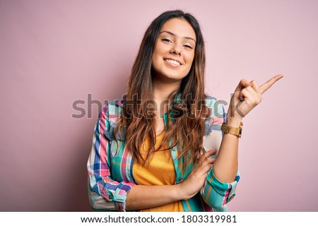 Photo of  Young beautiful brunette woman wearing casual colorful shirt standing over pink background with a big smile on face, pointing with hand and finger to the side looking at the camera.