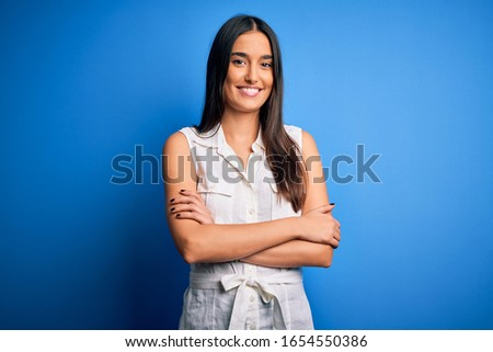 Young beautiful brunette woman wearing casual dress over isolated blue background happy face smiling with crossed arms looking at the camera. Positive person. Foto stock ©