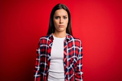 Young beautiful brunette woman wearing casual shirt standing over isolated red background skeptic and nervous, frowning upset because of problem. Negative person.