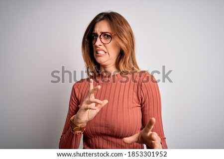 Young beautiful brunette woman wearing casual sweater and glasses over white background disgusted expression, displeased and fearful doing disgust face because aversion reaction. With hands raised Foto stock ©