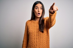Young beautiful brunette woman wearing casual sweater over isolated white background Pointing with finger surprised ahead, open mouth amazed expression, something on the front