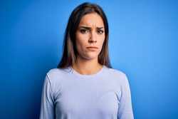 Young beautiful brunette woman wearing casual sweater standing over blue background skeptic and nervous, frowning upset because of problem. Negative person.