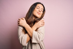 Young beautiful brunette woman wearing casual sweater standing over pink background Hugging oneself happy and positive, smiling confident. Self love and self care