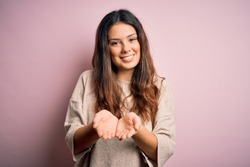 Young beautiful brunette woman wearing casual sweater standing over pink background Smiling with hands palms together receiving or giving gesture. Hold and protection