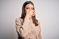 Young beautiful brunette woman wearing casual sweater standing over white background smelling something stinky and disgusting, intolerable smell, holding breath with fingers on nose. Bad smell