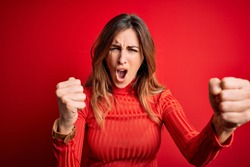Young beautiful brunette woman wearing casual turtleneck sweater over red background angry and mad raising fists frustrated and furious while shouting with anger. Rage and aggressive concept.