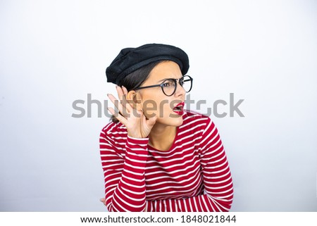 Young beautiful brunette woman wearing french beret and glasses over white background surprised with hand over ear listening an hearing to rumor or gossip Photo stock ©