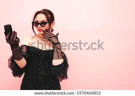 Young beautiful brunette woman wearing nice trendy summer polka-dot dress and gloves.Sexy fashion model posing near light pink wall in studio.Fashionable female in sunglasses.Looking in small mirror