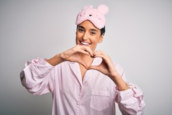 Young beautiful brunette woman wearing pajama and sleep mask over white background smiling in love doing heart symbol shape with hands. Romantic concept.