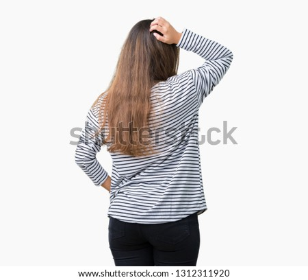 Young beautiful brunette woman wearing stripes sweater over isolated background Backwards thinking about doubt with hand on head
