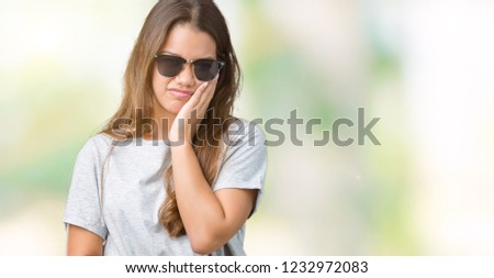 Young beautiful brunette woman wearing sunglasses over isolated background thinking looking tired and bored with depression problems with crossed arms. #1232972083