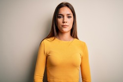 Young beautiful brunette woman wearing yellow casual t-shirt over white background with serious expression on face. Simple and natural looking at the camera.