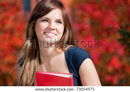 Young beautiful business woman hoding diary at city park. Student