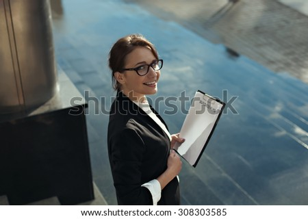 Photo of Young beautiful business woman thinking of her plans and smilling. Business lady manager doing business plan. Business people concept.
