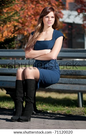 Young beautiful business woman waiting a meeting at autumn city park. Student