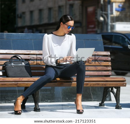 Young beautiful business woman working on a laptop #217123351