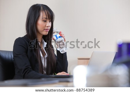 Young beautiful businesswoman drinking water at work