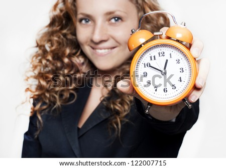 Young beautiful businesswoman holding a clock