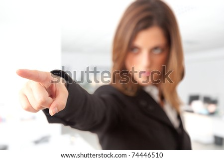 Young beautiful businesswoman pointing somebody responsible. Focus on finger.