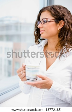 Young beautiful businesswoman taking break, standing in front of office window, holding coffee cup, looking away, smiling.