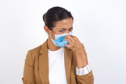 Young beautiful businesswoman wearing medical mask standing against yellow background, holding her nose because of a bad smell.