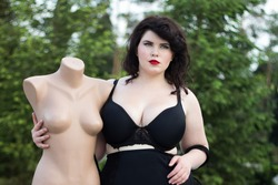 Young beautiful busty curvy  plus size model with big breast in black bra holding mannequin, xxl woman, professional makeup and hairstyle