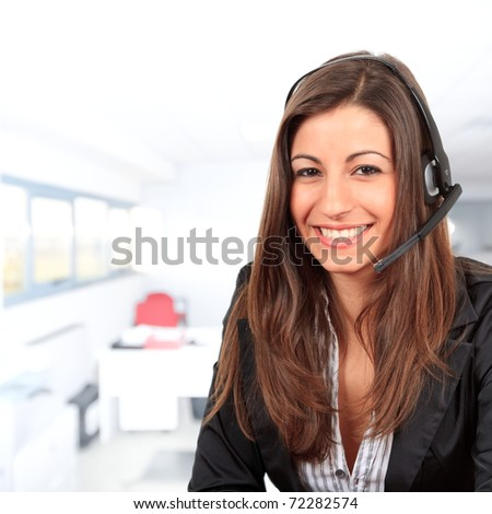 Young beautiful call center female operator in her office