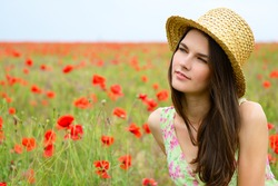 Young beautiful calm girl in straw hat dreaming on a poppy field, summer outdoor.