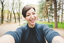 Young beautiful caucasian brown short hair woman happy taking selfie outdoor in the city - emancipation, happiness concept
