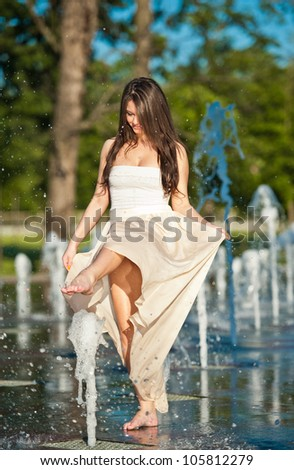young beautiful caucasian brunette girl playing at an outdoor water fountain .Sunny day